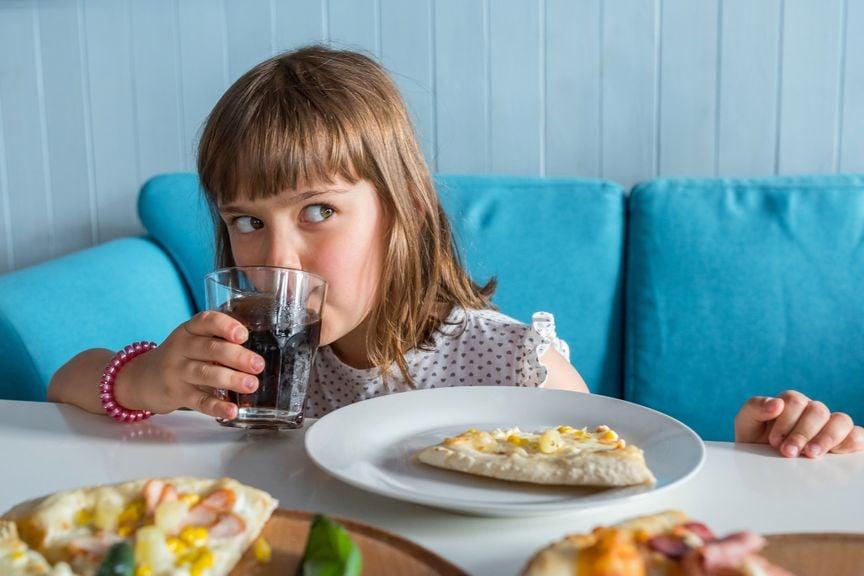 Mädchen isst Pizza und trinkt Cola