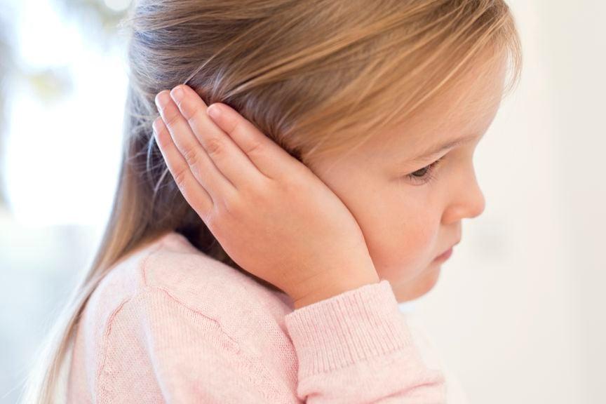 Kind hält sich das Ohr