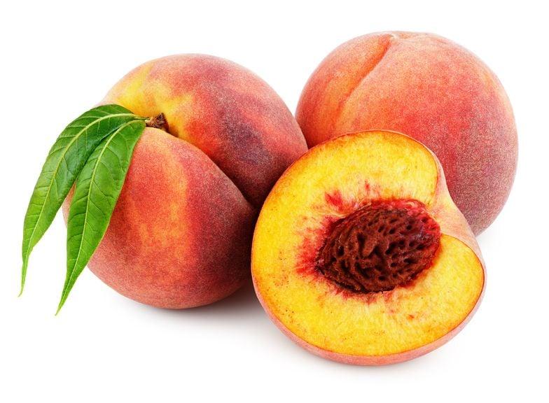 Pfirsiche, aufgeschnitten mit Kern und ganze Frucht