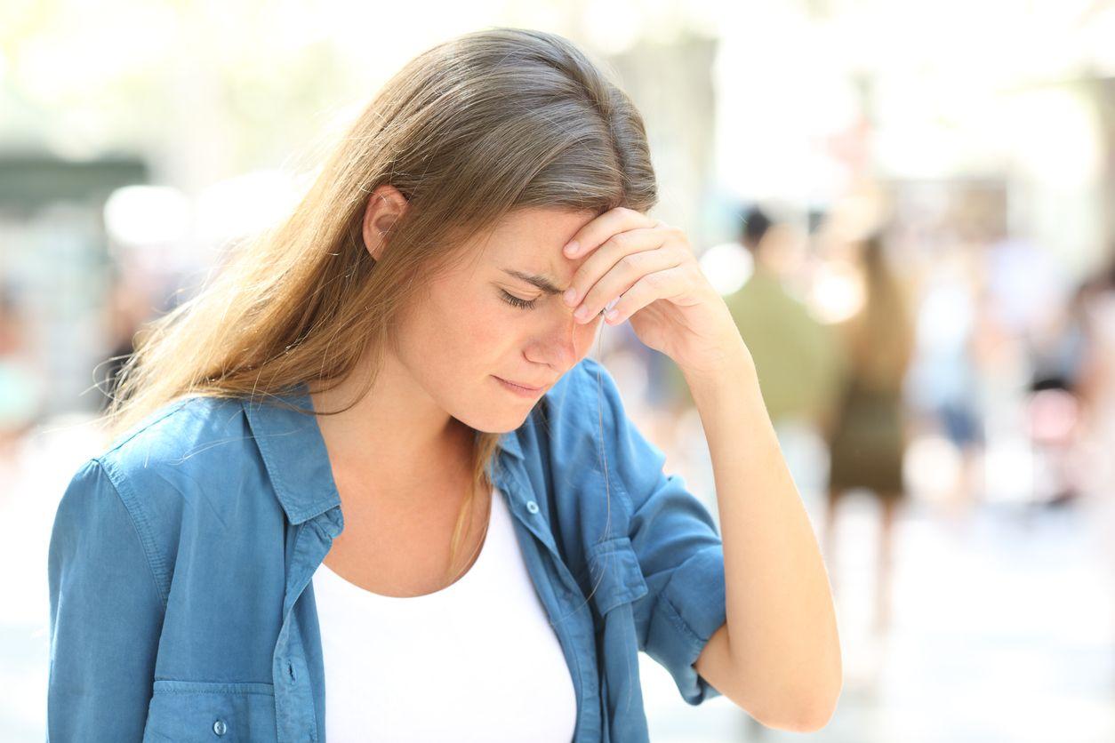 Frau hält die Hand an die Stirn wegen Kopfschmerz oder Schwindel