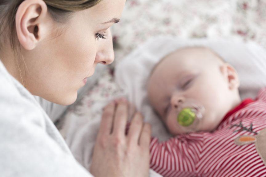 Mutter liegt neben schlafendem Baby,Mutter streichelt die Hand vom schlafendem Säugling