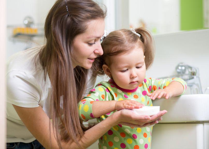 Mutter gibt Tochter die Seife zum Händewaschen
