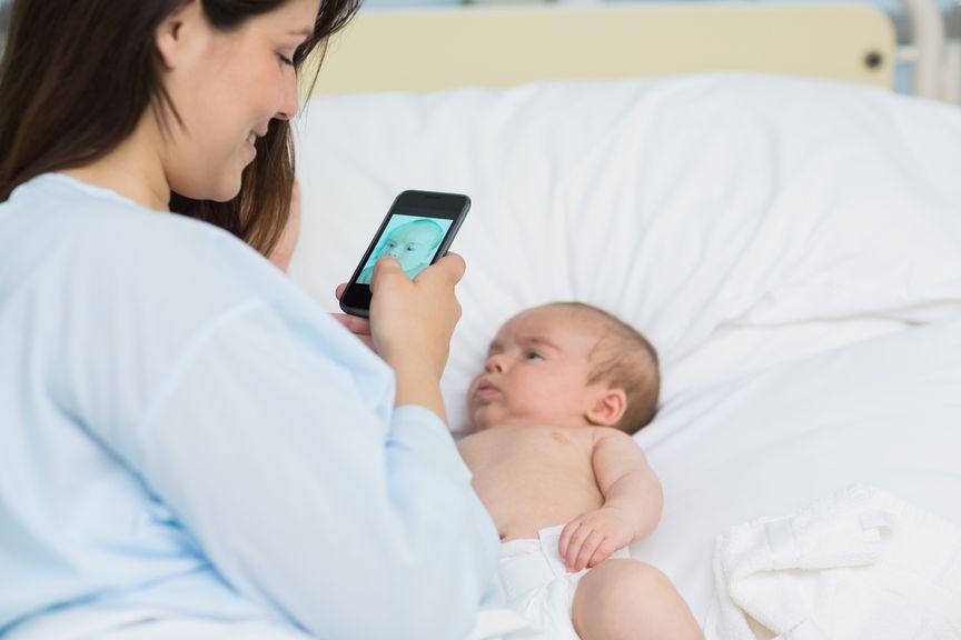 Junge Mutter fotografiert ihr Neugeborenes