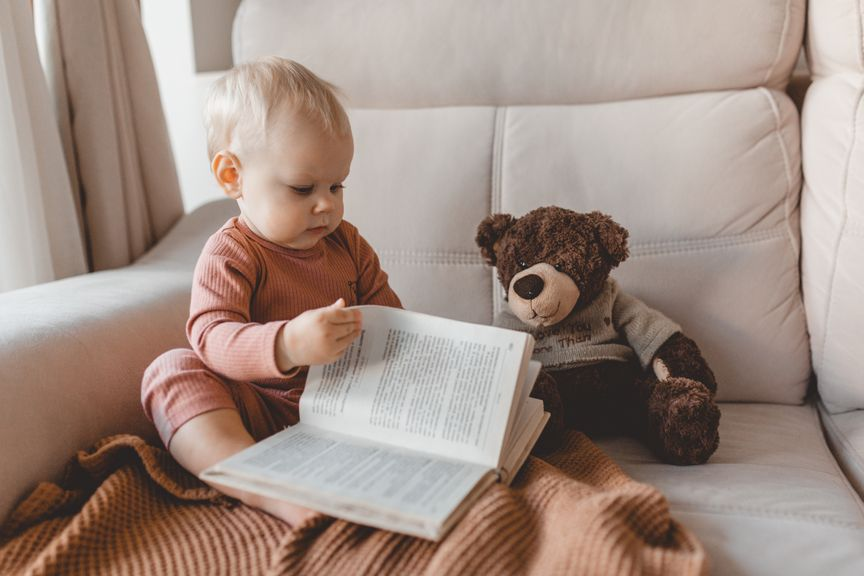 Kleinkind blättert in einem Buch, Teddybär sitzt daneben