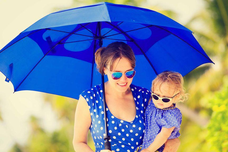 Mutter mit aufgespanntem Regenschirm mit Kind auf dem Arm