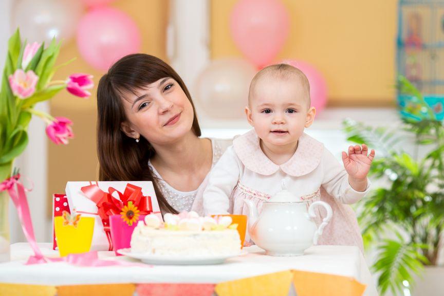 festlich gekleidetes Baby mit Mutter und Kuchen
