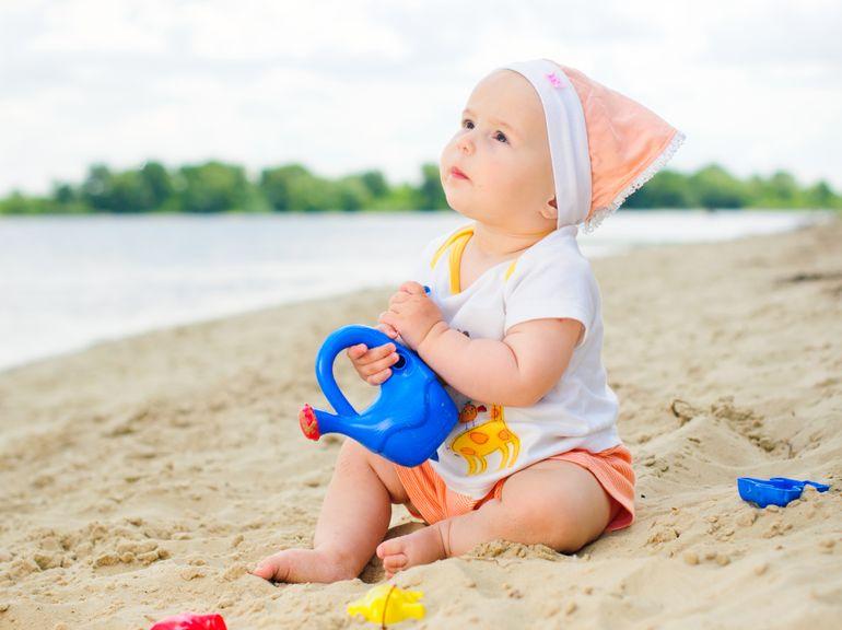 Baby mit Spielzeug am Strand