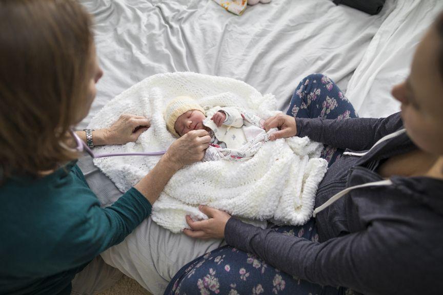 Hebamme untersucht Neugeborenes zu Hause