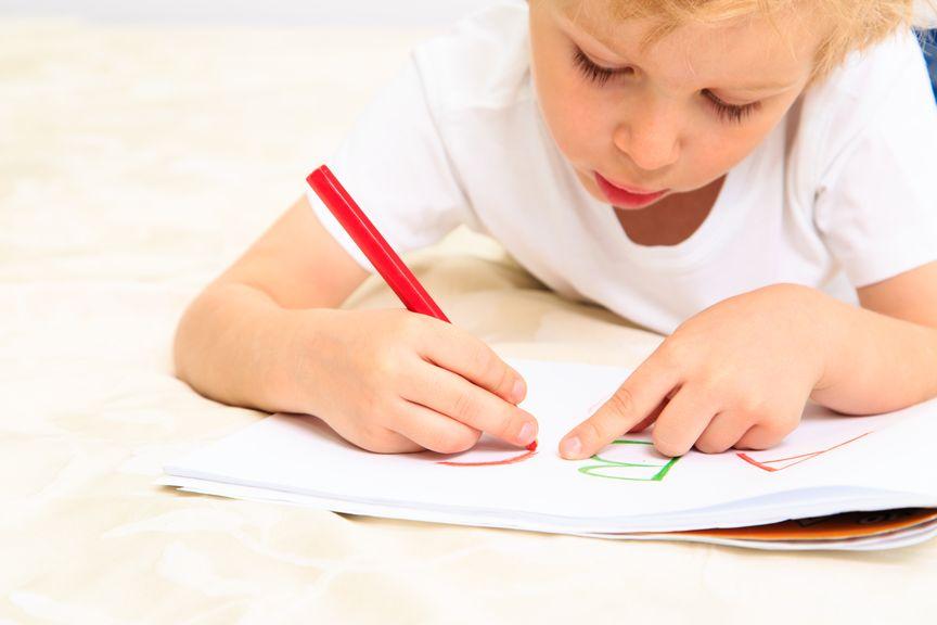 Kind schreibt bäuchlings in sein Heft