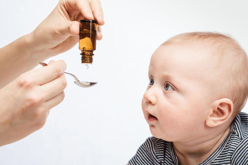 Baby bekommt Medkament als Tropfen auf Löffel