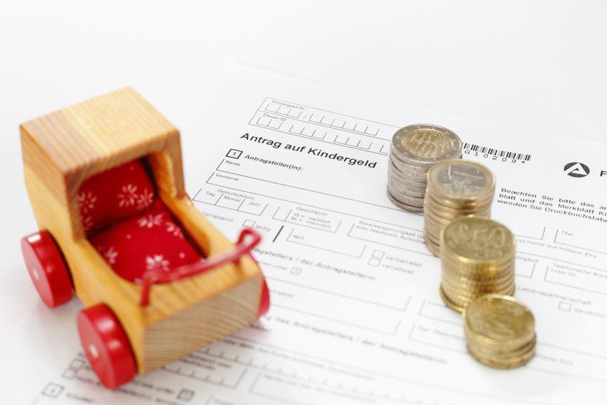 Antrag mit Münzen und Holzkinderwagen
