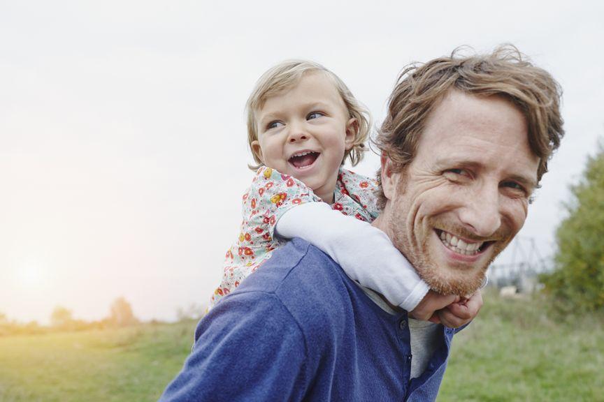 Vater mit kleiner Tochter auf dem Rücken