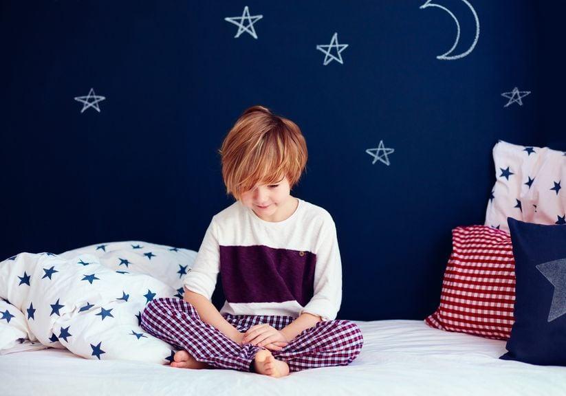Junge sitzt im Bett, ruhig und fertig zum Schlafengehen
