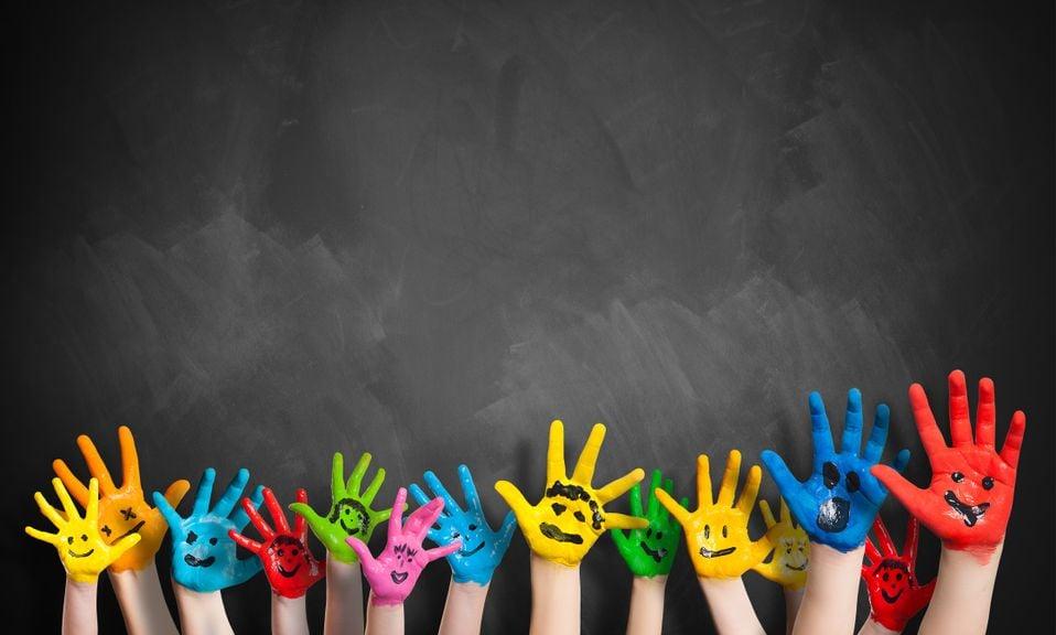 Bunt bemalte Hände vor einer Wandtafel