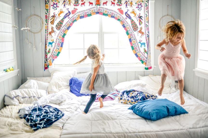 Mädchen hüpfen auf dem Bett herum