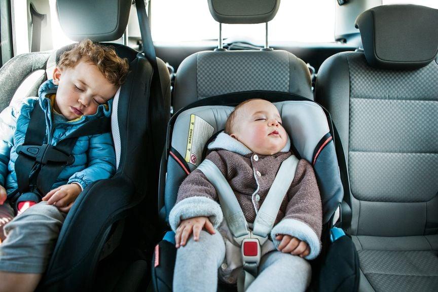Kind und Baby schlafen in Kindersitzen im Auto
