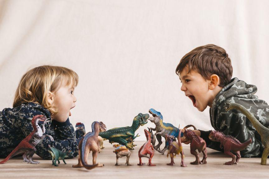 Kinder spielen mit Dinosauriern