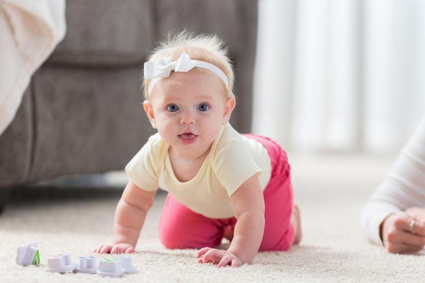 Baby krabbelt auf dem Teppich