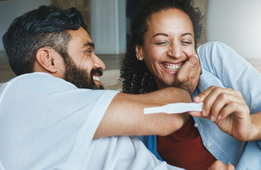 Paar freut sich über den positiven Schwangerschaftstest