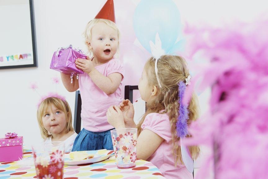 Kind an Geburtstagsparty mit Geschenk in der Hand