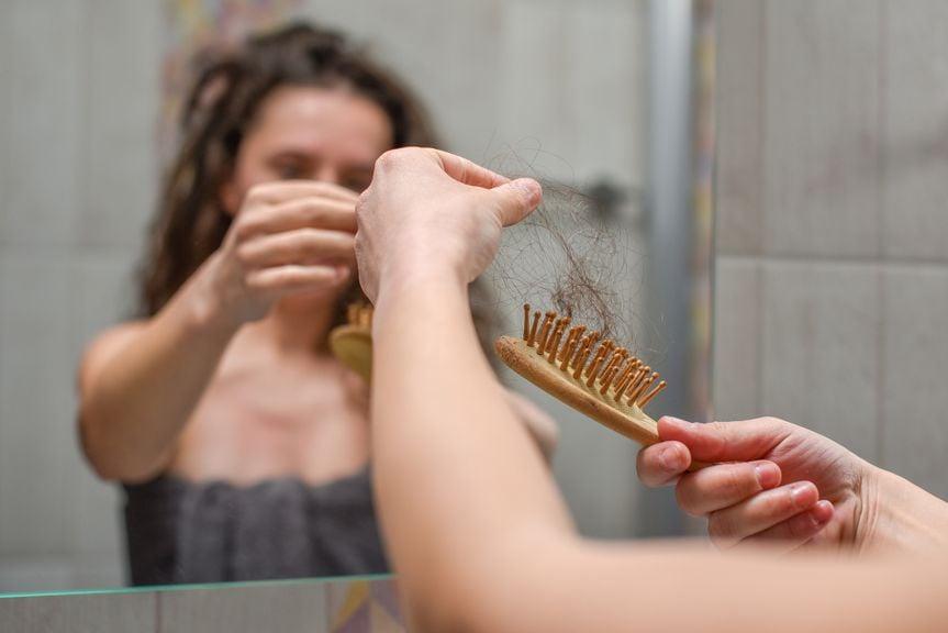 Frau zieht Haarbüschel aus der Bürste