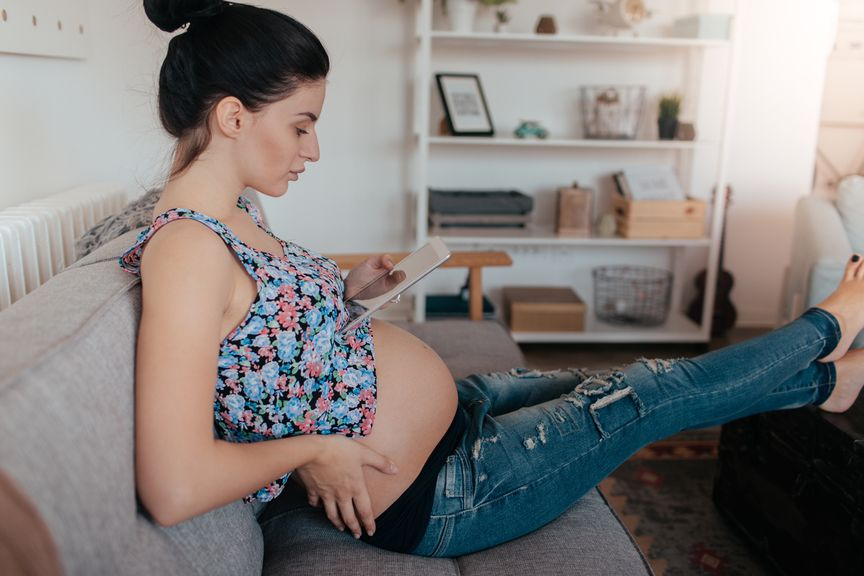 Schwangere hat die Beine hochgelegt und liest im Tablet
