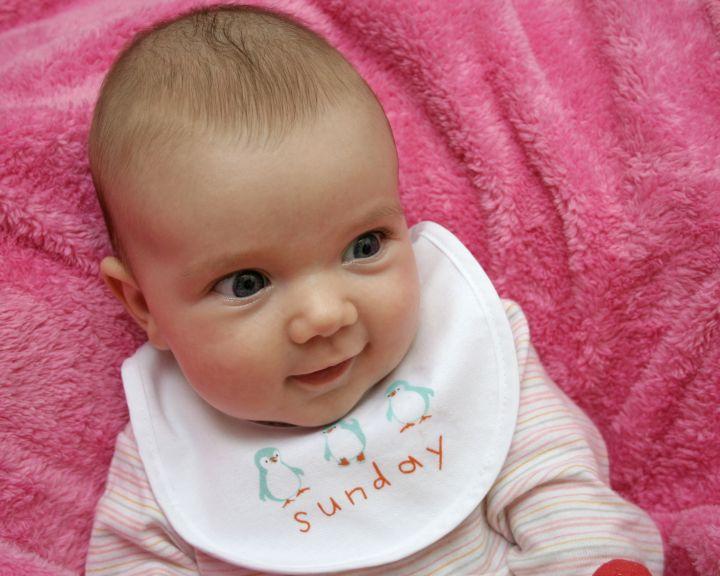 Baby mit Latz auf einer rosa Decke