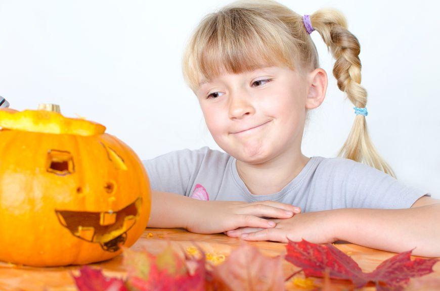 Mädchen mit Kürbis und Herbstblättern