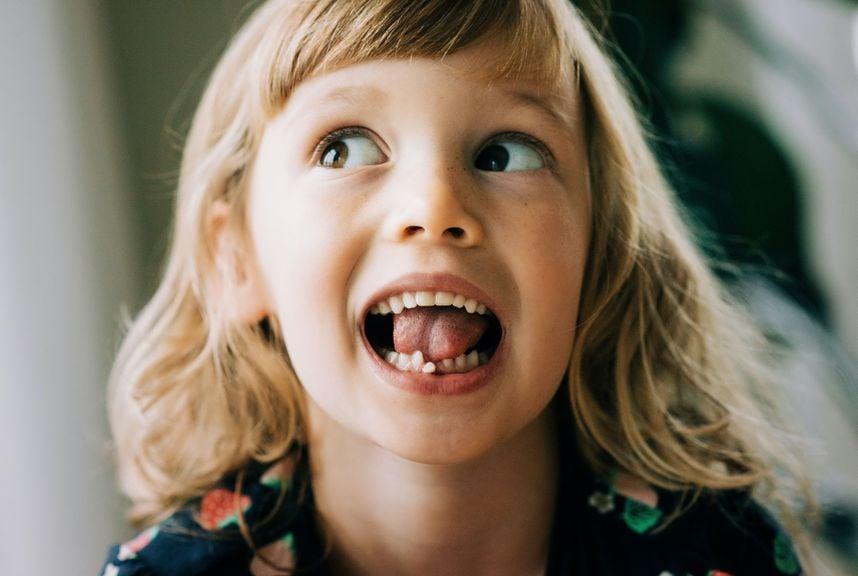 Zunge drückt gegen wackelnden Milchzahn