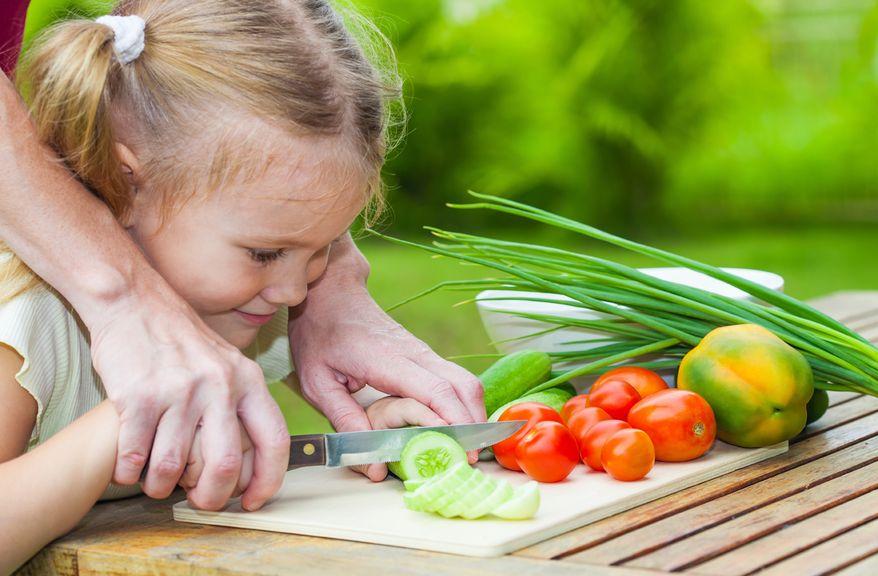 Kind hilft beim Rüsten ,Mädchen beim Gemüserüsten