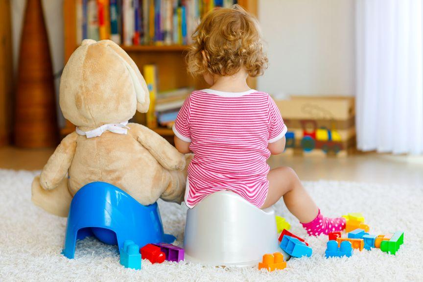 Kind und Teddy sitzen auf einem Töpfchen