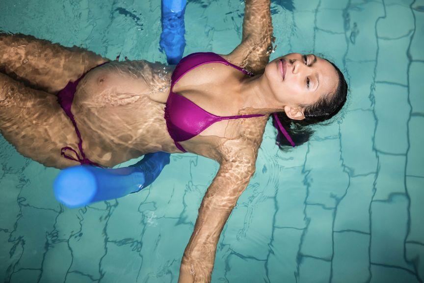Schwangere mit Poolnudel im Wasser