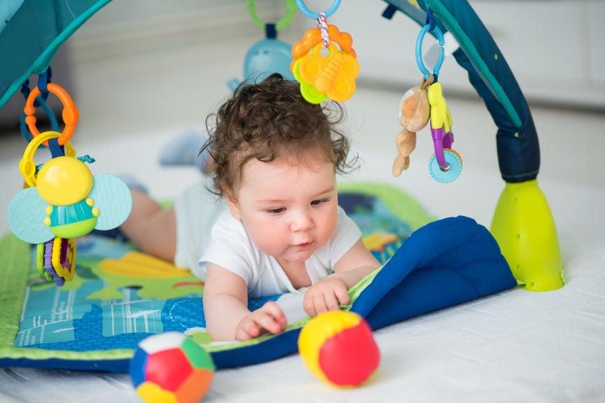 Baby umgeben von Spielbogen und buntem Spielzeug