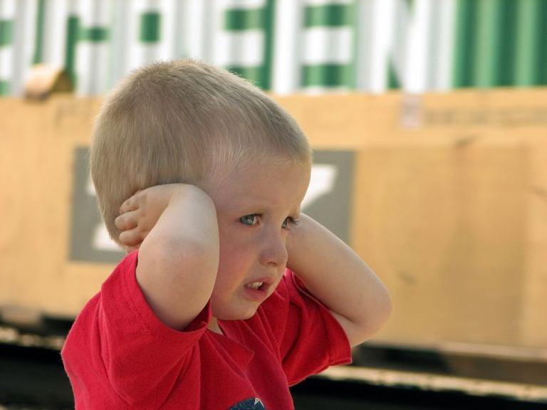 Junge hält sich ängstlich beide Ohren zu