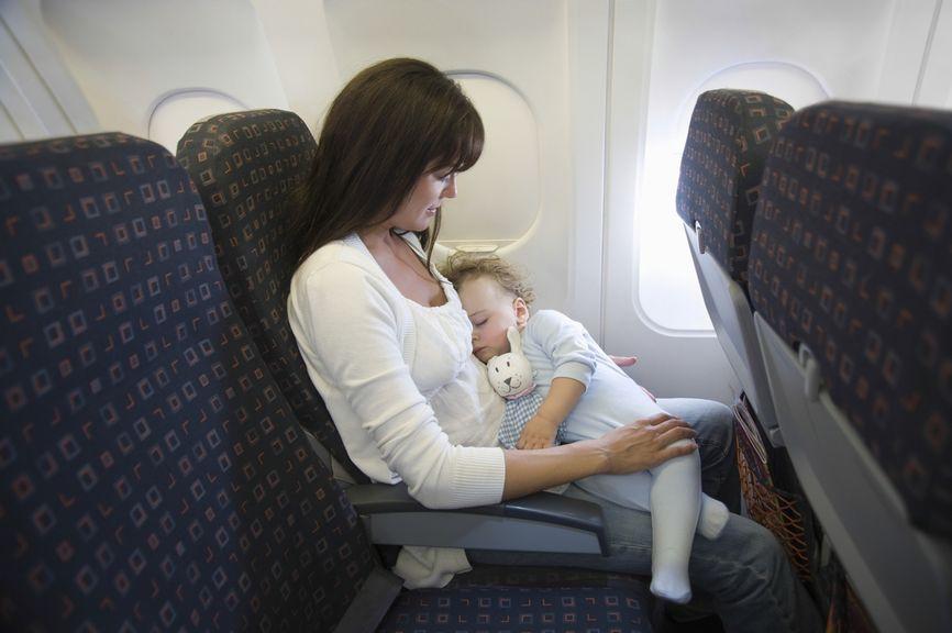 Mutter hält ihr schlafendes Baby während dem Flug