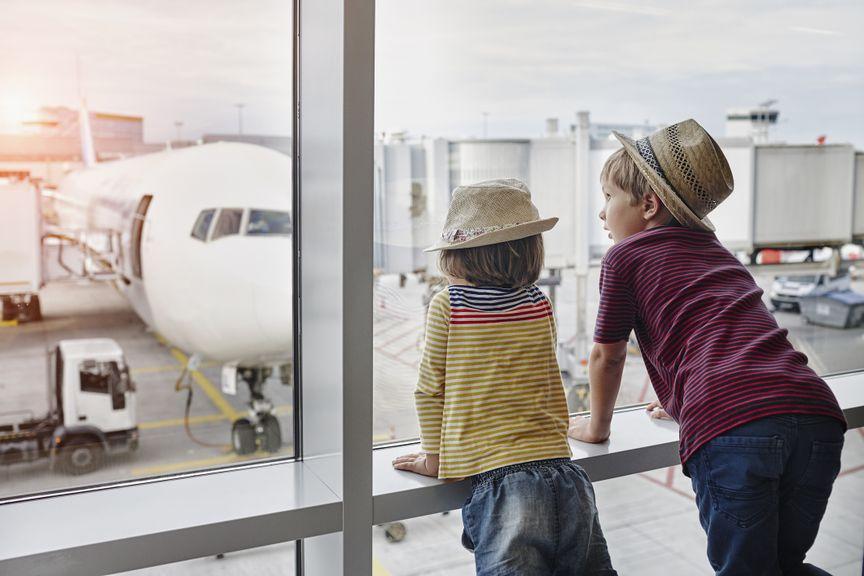 Zwei Kinder bestaunen Flugzeug am Flughafen