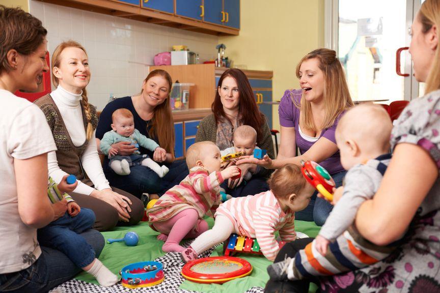 mehrere Mütter sitzen mit ihren Babys im Kreis am Boden