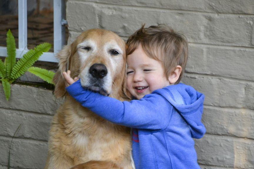 Kind umarmt seinen Hund