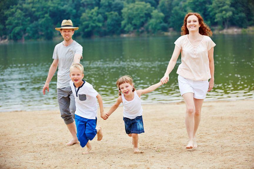 Familienferien am Strand; Eltern und zwei Kleinkinder gehen spazieren am sandigen Seeufer