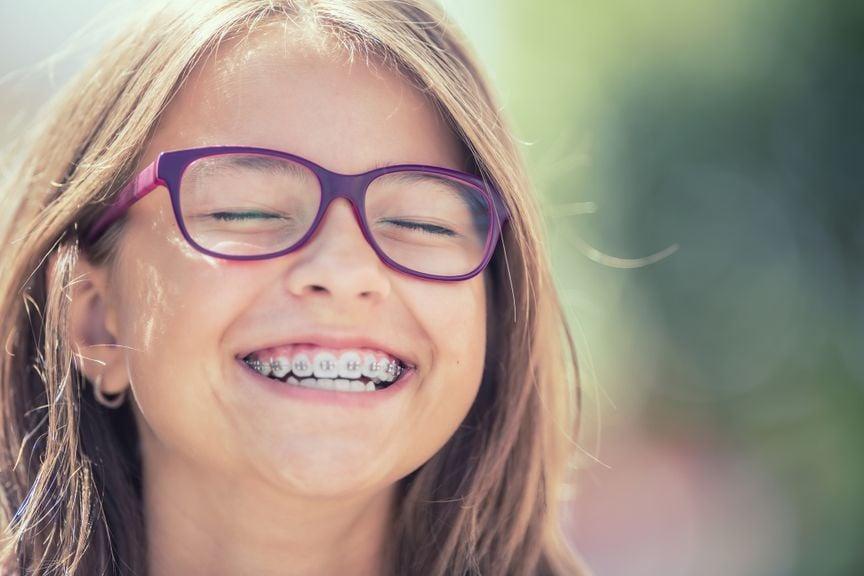 Mädchen mit Zahnspange und Brille