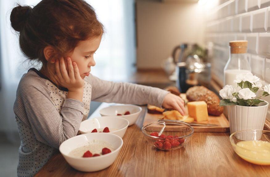 Mädchen richtet in der Küche das Morgenessen