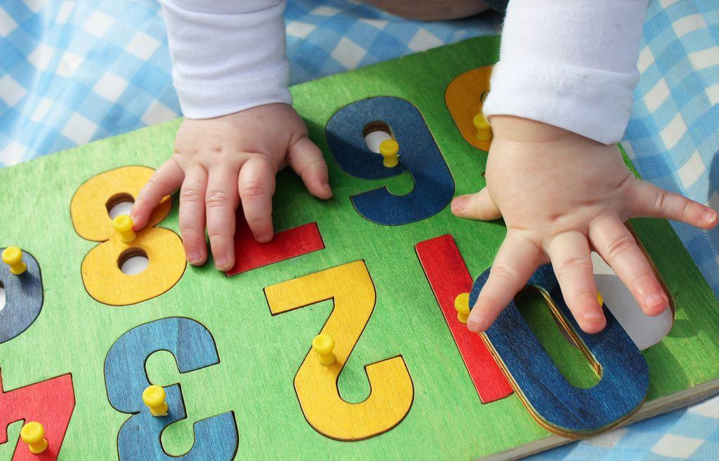 Babyhände auf einer bunten Holzplatte mit Zahlen
