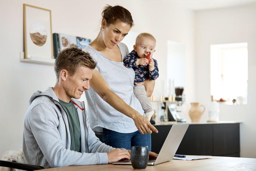 Paar mit Baby recherchiert am Laptop