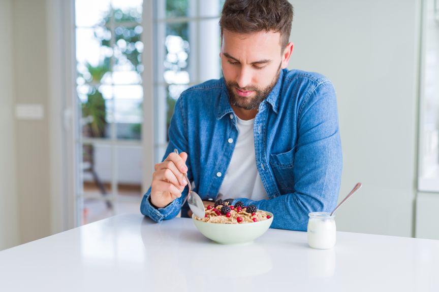 Mann isst Müsli mit Beeren