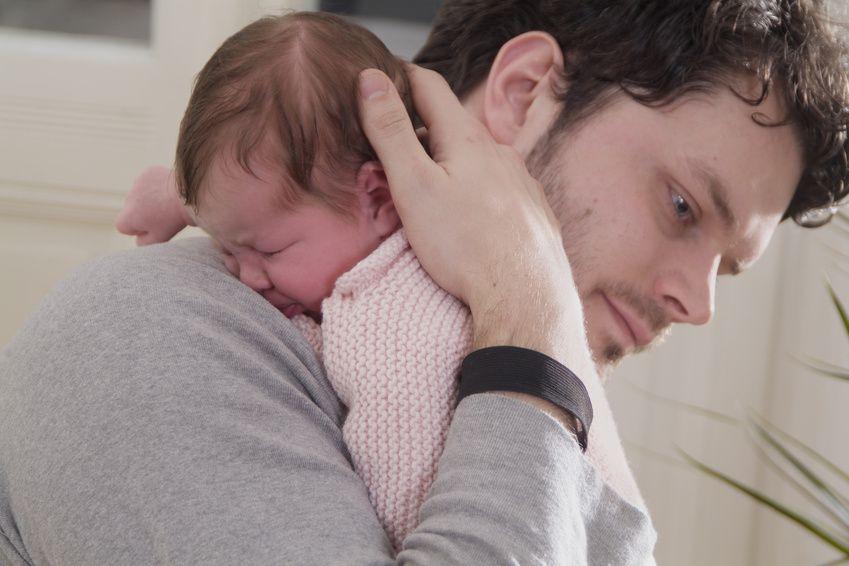 Vater hält Baby über der Schulter