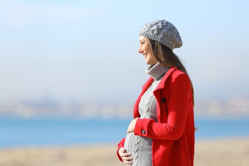 Schwangere am Meer in der Wintersonne
