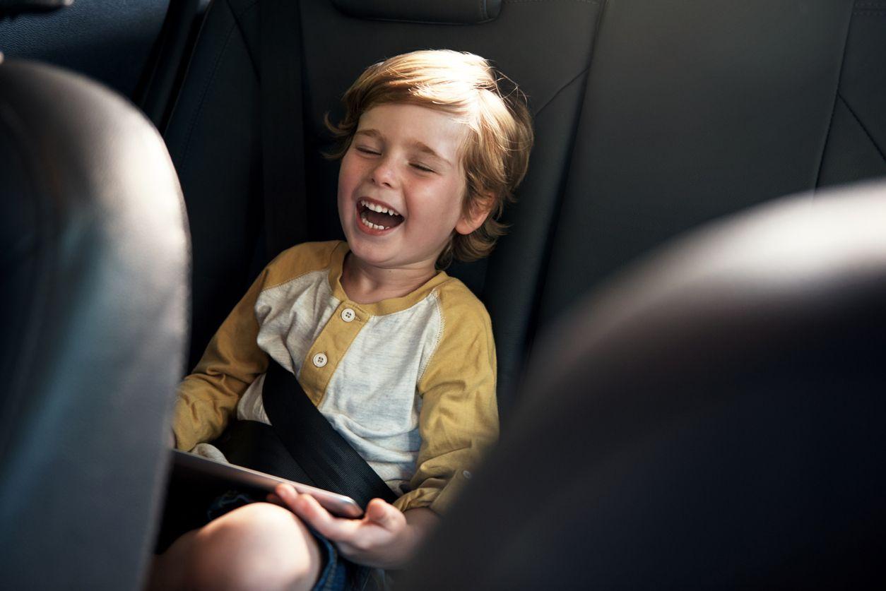 Kind sitzt lachend im Auto