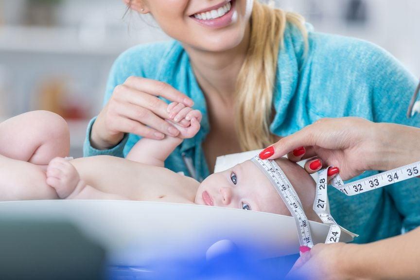 Mutter mit Baby beim Kinderarzt, Kopfumfang wird gemessen