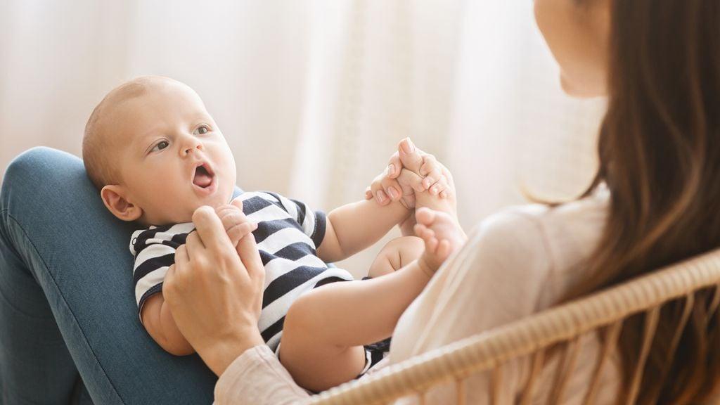 Baby liegt auf den Beinen seiner Mutter
