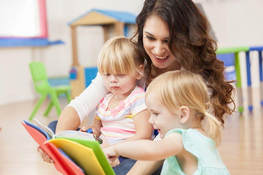 Kinder schauen, mit der Tagesbetreuung, ein Buch an
